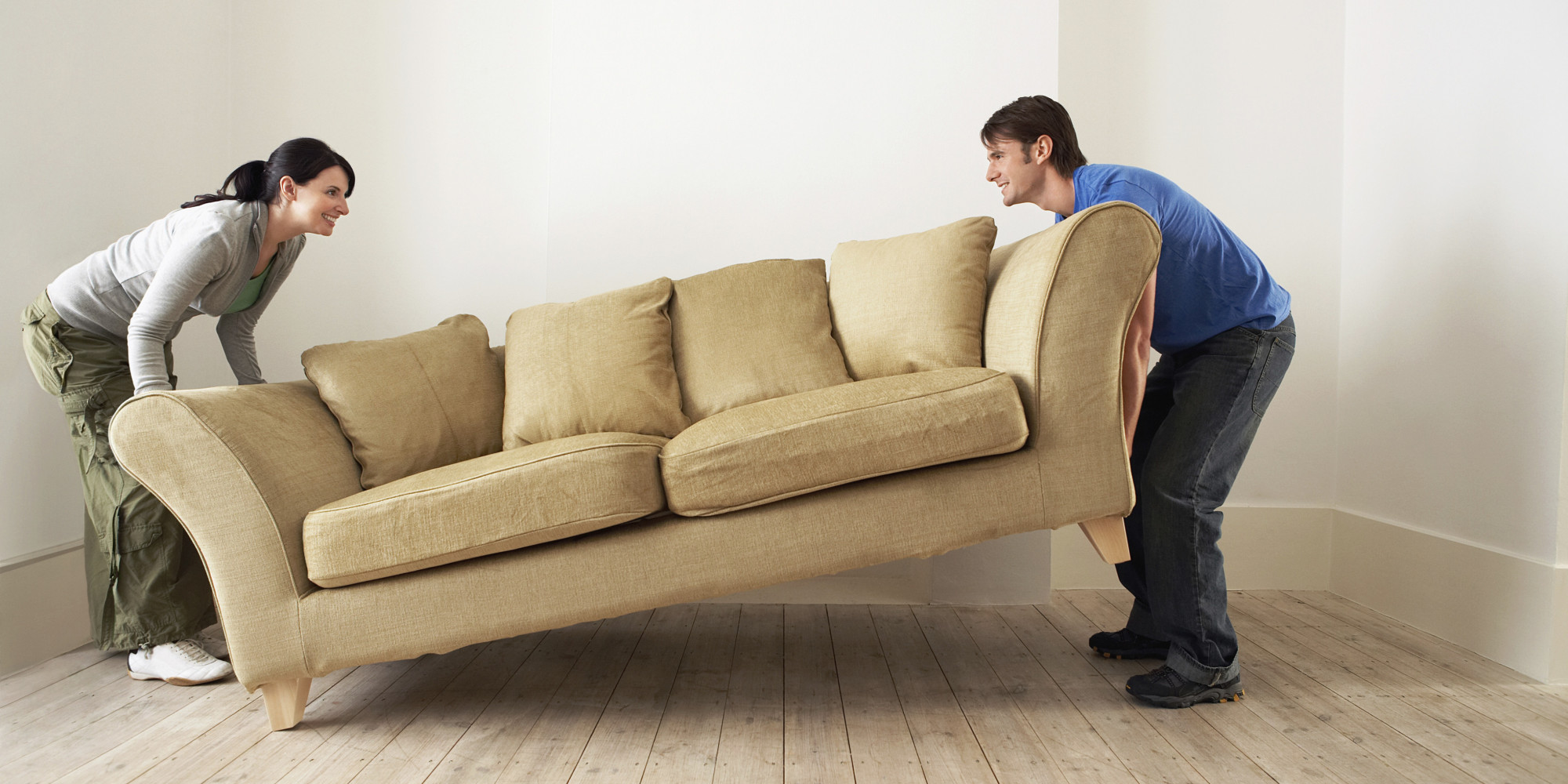 Couple Placing Sofa In Living Room Of New Home